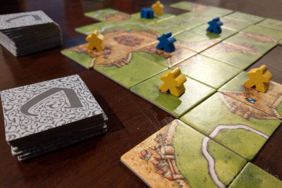 carcassonne with yellow and blue meeples and tiles