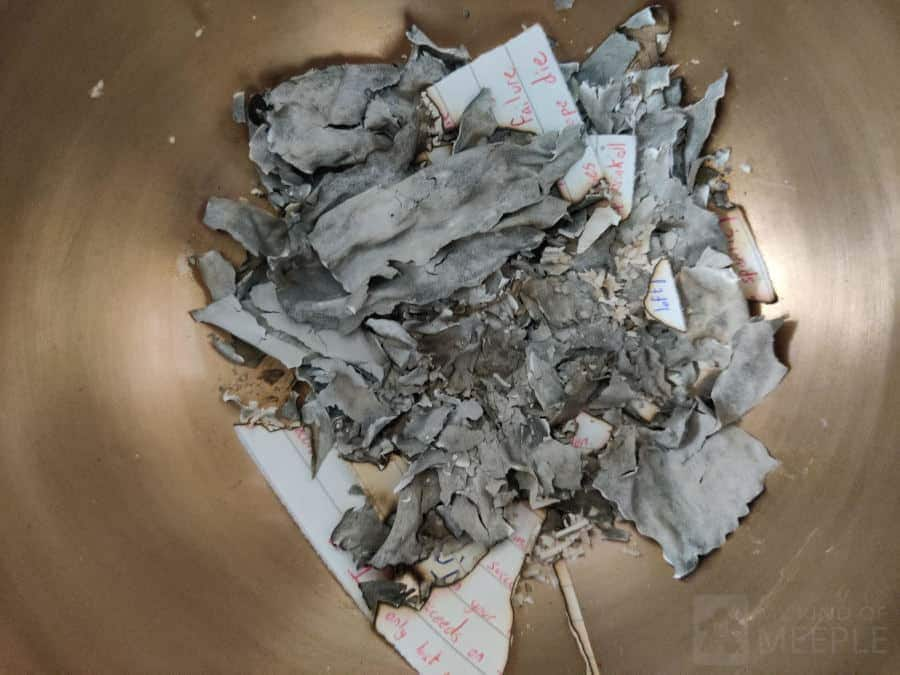 The burnt paper at the end of the game in the fireproof bowl